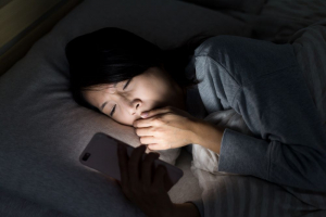 A woman lying in bed on her side in a dark room, illuminated by the screen of her phone. She is yawning and covering her mouth with her left hand, whilst her right holds her phone.