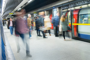 picture of commuters waiting for train. Long exposure picture, commuters and train arriving are both blurred.